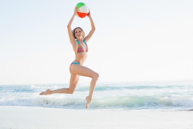 Giovane donna allegra che salta sulla spiaggia