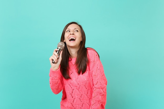 Giovane donna allegra in maglione rosa lavorato a maglia che cerca tenere in mano, cantare una canzone nel microfono isolato su sfondo blu turchese muro, ritratto in studio. concetto di stile di vita della gente. mock up copia spazio.