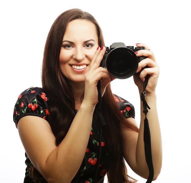 Giovane donna allegra che fa foto sulla macchina fotografica sopra fondo bianco