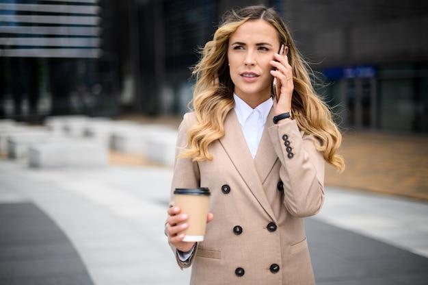 Allegro giovane donna al telefono all'aperto in un moderno contesto urbano