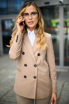 Giovane donna allegra al telefono all'aperto in un ambiente urbano moderno