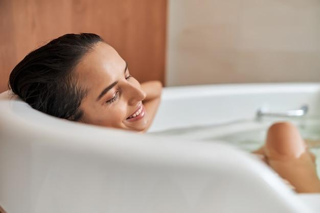 Giovane donna allegra che si rilassa nella vasca da bagno a casa