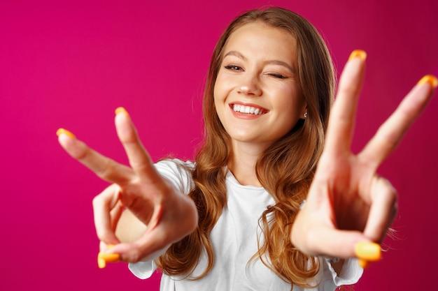 Giovane donna allegra che mostra il segno della mano di vittoria