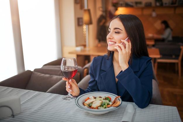 La giovane donna allegra si siede alla tavola e parla sul telefono.