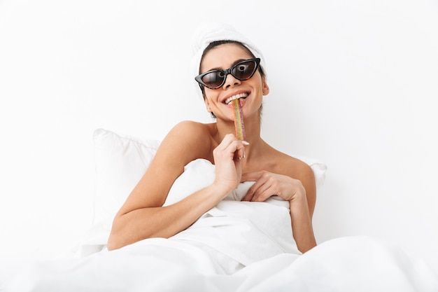 Allegra giovane donna seduta a letto dopo la doccia avvolta in una coperta, indossando occhiali da sole, mangiando caramelle