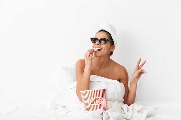 Allegra giovane donna seduta a letto dopo la doccia avvolta in una coperta, indossando occhiali da sole, mangiando popcorn
