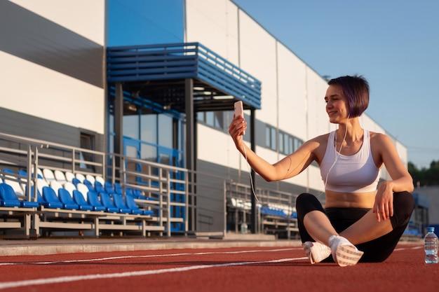 Una giovane donna allegra in abbigliamento sportivo che si rilassa dopo un allenamento o una corsa, seduta su una pista dello stadio, facendo selfie, ascoltando musica con le cuffie sul suo smartphone, facendo una pausa durante un allenamento
