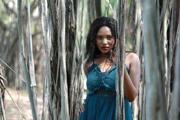 Giovane donna allegra che fa una pausa un albero nella giungla.