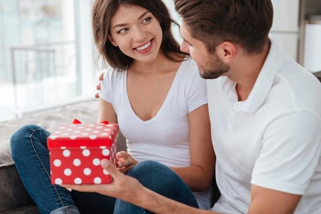 Giovane donna allegra che prende regalo dal suo ragazzo a casa