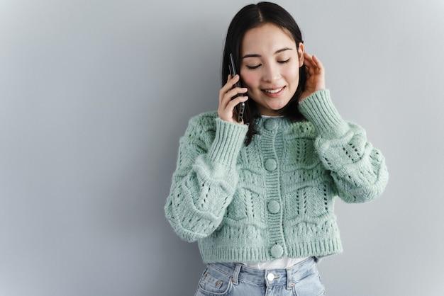 Giovane donna allegra parlando al telefono cellulare isolato su sfondo grigio