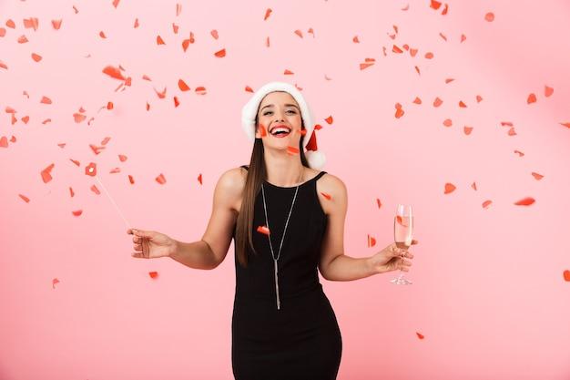 Allegro giovane donna che indossa il cappello di natale in piedi isolato su sfondo rosa, con in mano un bicchiere di champagne frizzante, celebrando