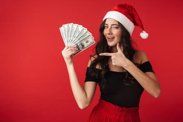 Allegro giovane donna che indossa il cappello di natale in piedi isolato su rosso, mostrando le banconote in denaro