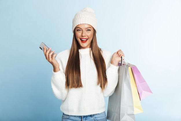 Allegro giovane donna che indossa un maglione, tenendo il telefono cellulare, portando le borse della spesa