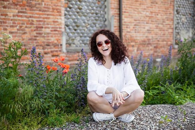 Allegra giovane donna con i capelli ricci guarda la telecamera e sorride, indossa occhiali da sole, seduta nel parco, intorno ai fiori, isolata di un edificio con sfondo di mattoni rossi.