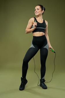 Giovane donna allegra con la corda per saltare in piedi in studio