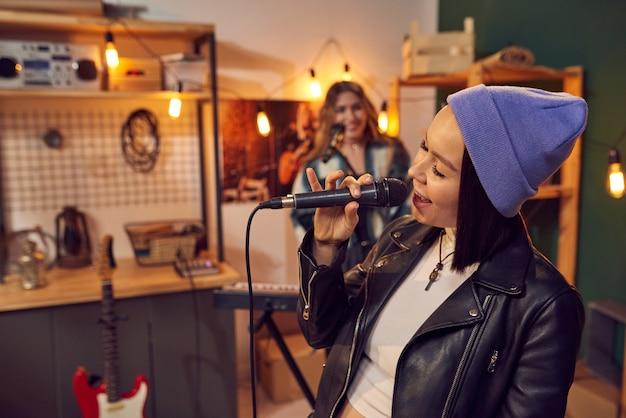 Giovane donna allegra con il microfono che canta contro la sua amica che suona la tastiera