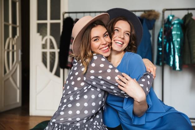 Giovani donne allegre che abbracciano all'interno nella sala d'esposizione del negozio