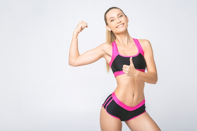 Donna sportiva sorridente allegramente bella che dimostra bicipite, isolato su priorità bassa bianca