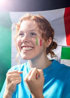 Donna sorridente sorridente con la bandiera italiana sul volto