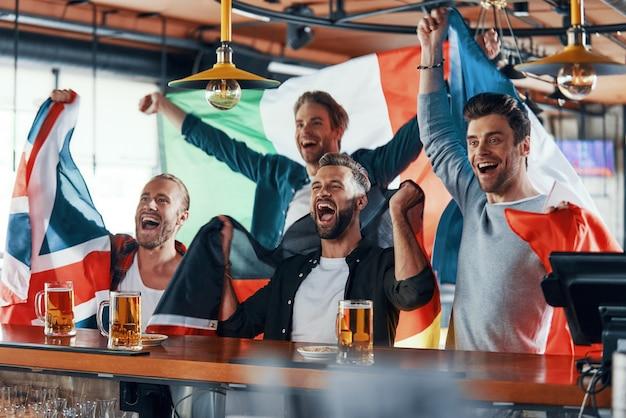 Giovani tifo ricoperti di bandiere internazionali che si godono la birra mentre guardano una partita sportiva al pub