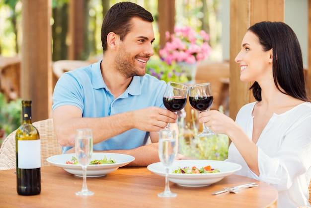 Saluti! bella giovane coppia di innamorati che tostano con vino rosso e sorridono mentre si rilassano insieme nel ristorante all'aperto