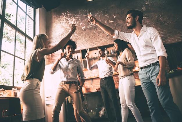 Saluti agli amici! inquadratura dal basso di giovani allegri che ballano e bevono mentre si godono la festa a casa in cucina