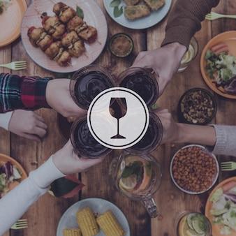 Saluti agli amici! vista dall'alto di quattro persone che esultano con vino rosso seduti al tavolo da pranzo rustico