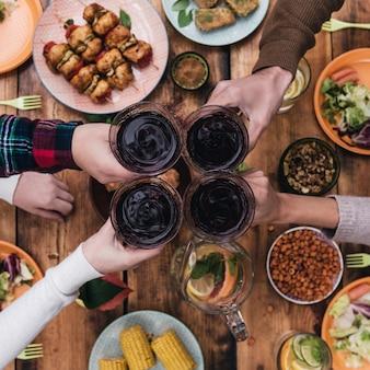 Saluti agli amici! vista dall'alto di quattro persone che applaudono con vino rosso