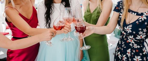 Saluti! le ragazze festeggiano e le mani si alzano con bicchieri di vino per brindisi