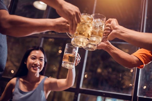 Saluti! gruppo, boccale da birra, le giovani donne preparano bicchieri da birra per celebrare il loro successo.