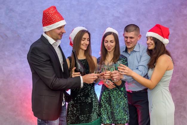 Saluti! un gruppo di amici festeggia e solleva bicchieri di champagne per brindisi, capodanno 2020
