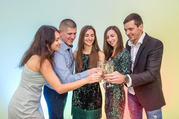 Saluti! un gruppo di amici festeggia e alza bicchieri di champagne per brindare, il nuovo anno 2020