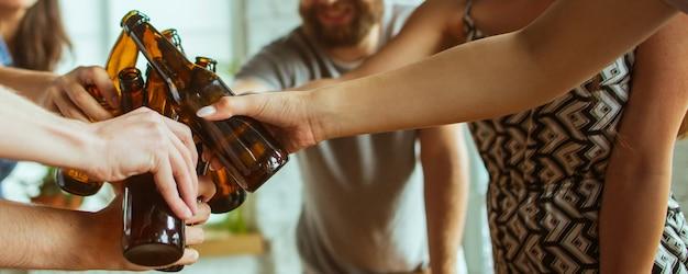 Saluti. mani di amici, colleghi mentre bevono birra, si divertono, tintinnano bottiglie, bicchieri insieme.