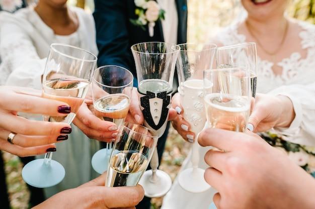 Saluti! gli sposi con gli amici bevono champagne all'aria aperta. la gente festeggia e solleva bicchieri di vino per brindare. un gruppo di uomini e donne celebra il matrimonio.
