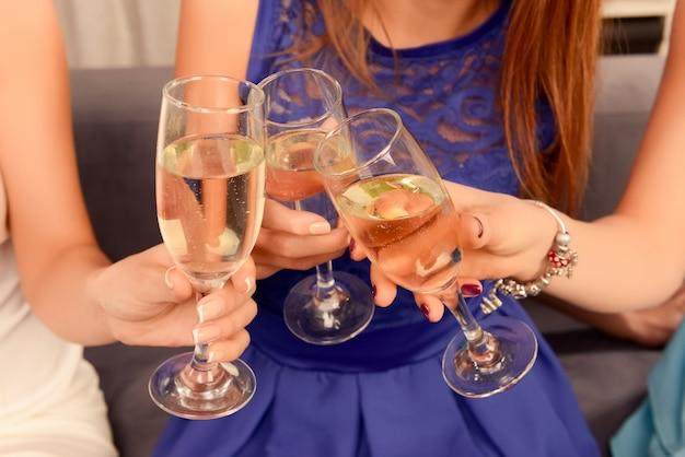 Saluti! tre amiche che hanno festa e bevono shampagne