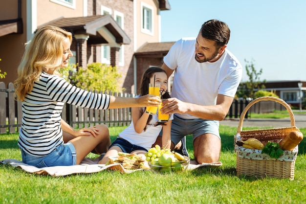 Saluti a noi. adorabile giovane famiglia che gode del picnic nel loro cortile e bicchieri tintinnanti con succo d'arancia