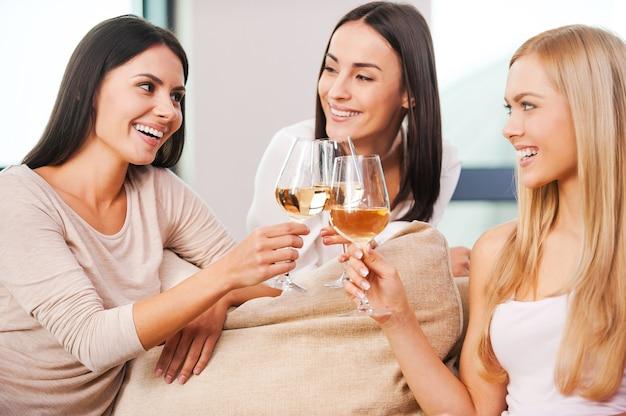 Saluti a noi! tre belle giovani donne che brindano con vino e sorridono