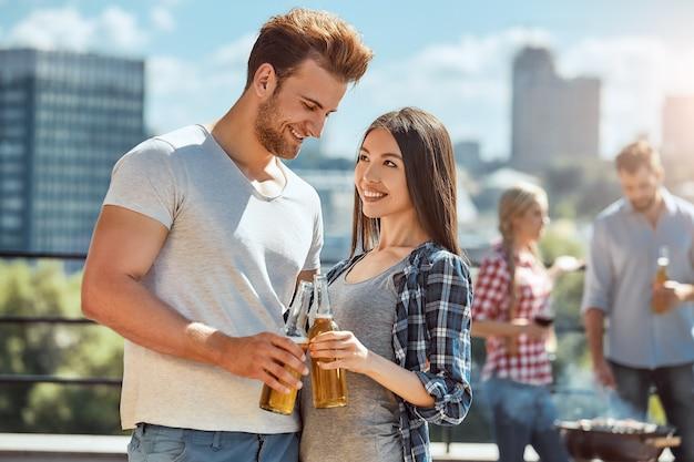 Saluti a noi giovani e adorabili coppie stanno facendo tintinnare bicchieri di birra e sorridendo mentre