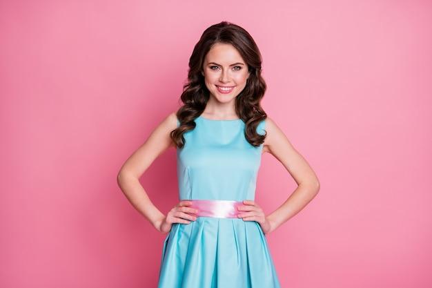 Allegra ragazza ondulata con le braccia conserte isolate su sfondo rosa color pastello