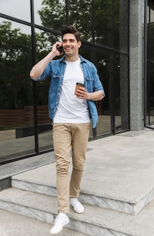 Giovanotto allegro in abiti casual che beve caffè da asporto e parla al cellulare mentre sta in piedi sopra l'edificio
