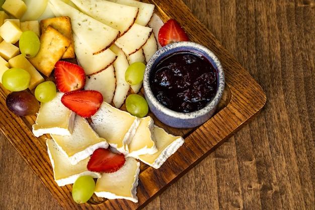 Formaggi assortiti con frutta e marmellata su tavola di legno. servire la tavola e gli spuntini al vino per il banchetto.