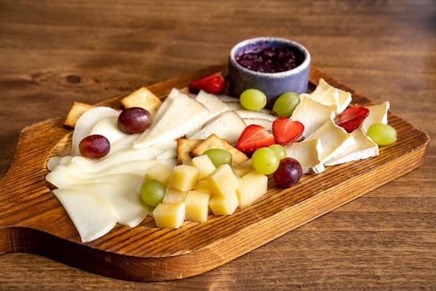 Formaggi assortiti con frutta su tavola di legno
