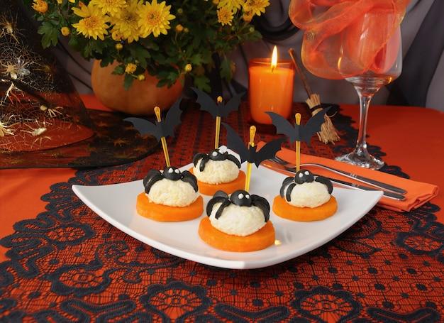 Palline di formaggio con ragni di olive e pipistrelli su un tavolo festivo