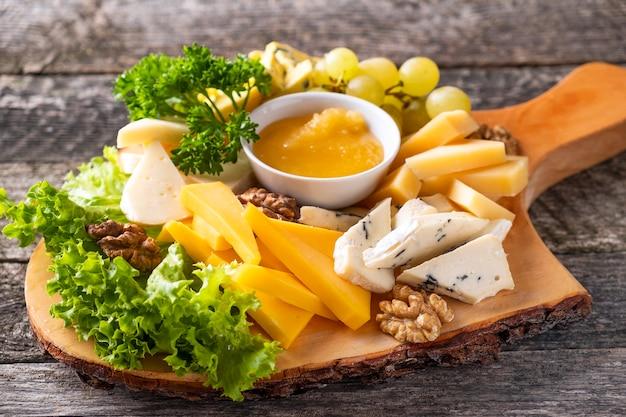 Tagliere di formaggi. diversi tipi di formaggio con miele, uva e noci su tavola di legno