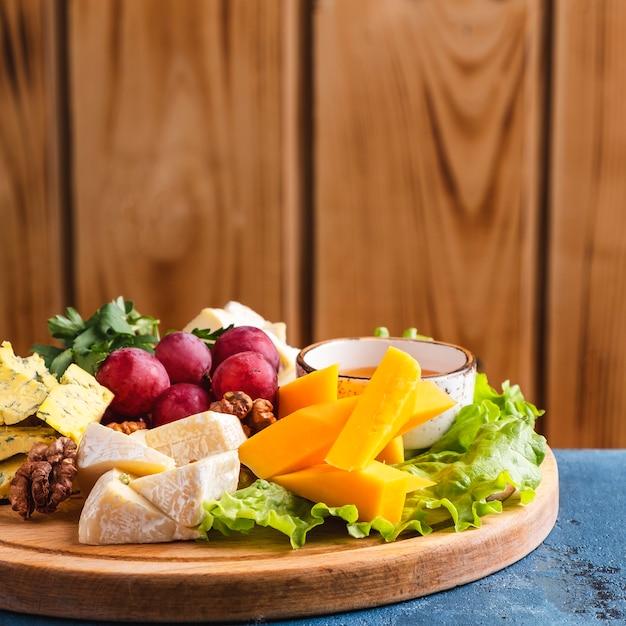 Piatto di formaggi servito con miele e uva rossa. copia spazio