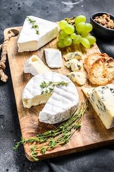 Tagliere di formaggi con camembert francese, brie e formaggio blu, uva e noci