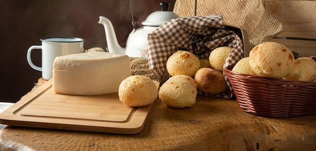 Pane al formaggio, composizione brasiliana per la colazione, pane al formaggio, formaggio bianco, bollitore e accessori, sfondo astratto scuro, fuoco selettivo.