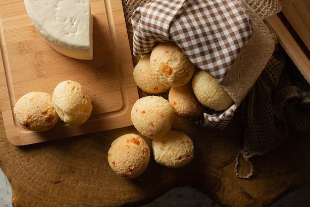 Pane al formaggio, disposizione della colazione brasiliana, pane al formaggio, formaggio bianco, bollitore e accessori, sfondo astratto scuro, vista dall'alto.