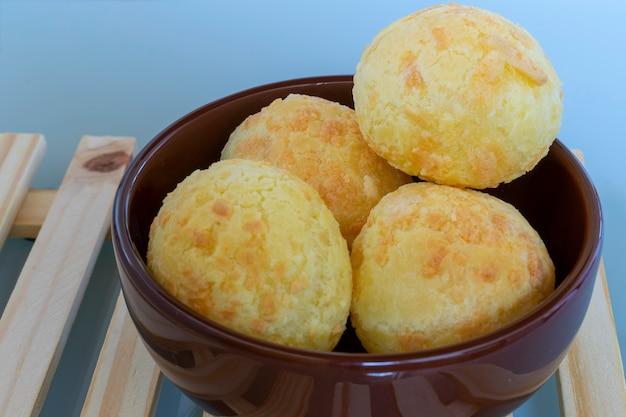 Pane al formaggio in ciotola marrone su pallet di legno.