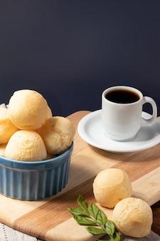 Pane al formaggio (pã£o de queijo) in una ciotola blu e caffè nero.
